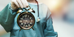 Surgeon holding clock